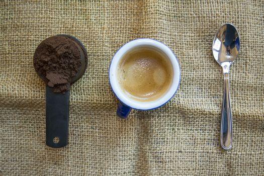 measuring of ground coffee next a short espresso