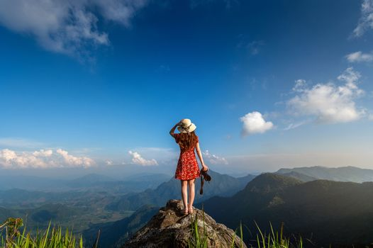 Woman hand holding camera and standing on top of the rock in nature. Travel concept.