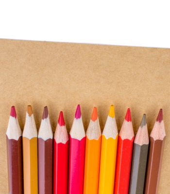 Color pencils  placed on  brown sheet of paper
