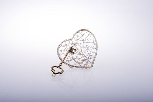Key and a heart shaped metal cage on white