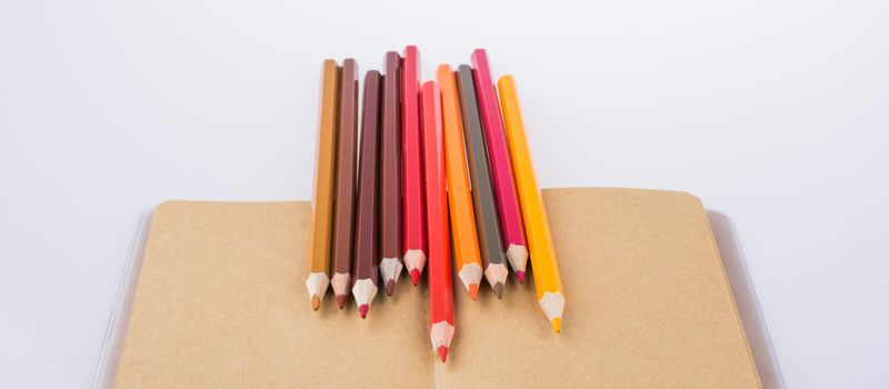 Color pencils placed on a brown notebook