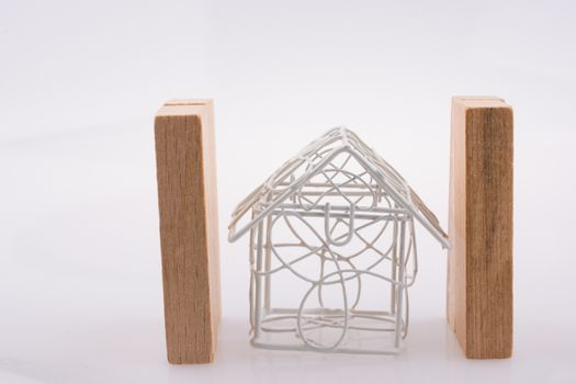 Little metal house  between two domino pieces  on a light  brown color background