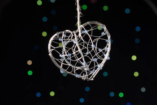 Heart shaped metal cage on a bokeh light background