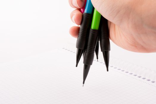 mechanical pencils of various color in hand on white background