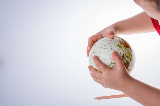 Child holding a globe and a pen in on a white background