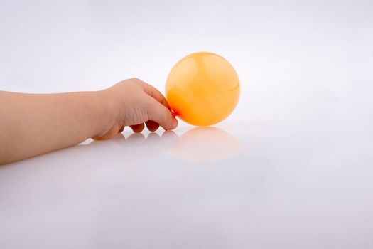 Hand holding a Colorful small balloon on a white background