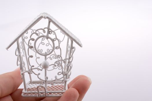 Little white metal bird house made of meta in handl