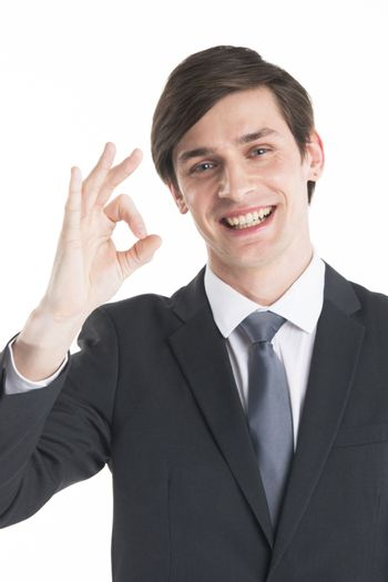 Everything is OK! Happy young business man in suit and tie gesturing OK sign and smiling standing isolated on white background