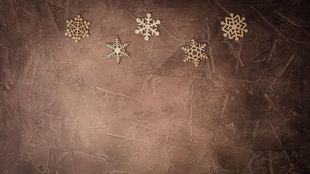 Handmade wooden snowflakes on the brown background, Christmas congratulation concept