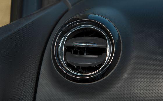 Car interior with closeup of ventilation grille for air conditio