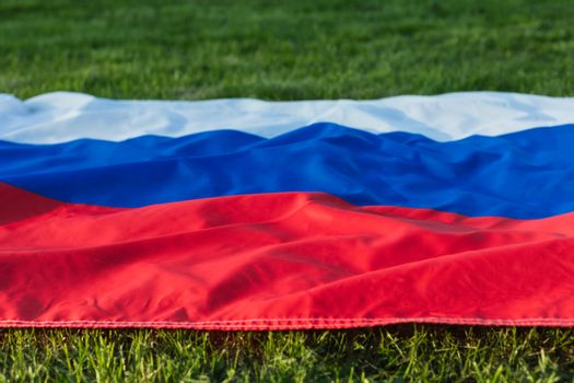 Russian flag lying on the green grass