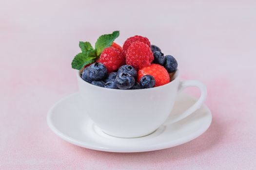 Fresh summer berries in the mug over the pink background
