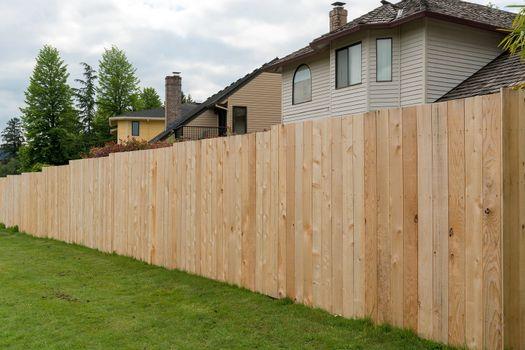 New Cedar wood fence boards along garden backyard of homes in suburban neighborhood