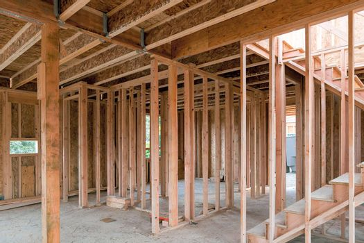 New home construction interior wood stud framing ceiling beams and stair