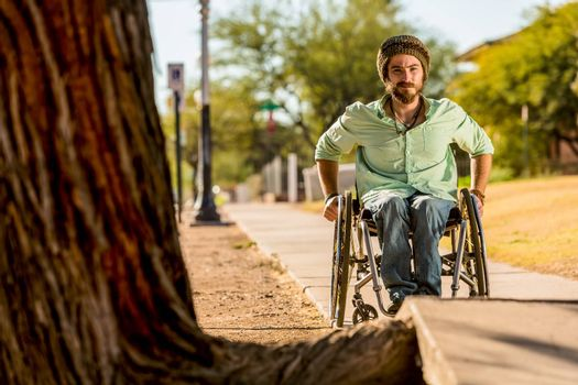 Man in a wheelchair looking over sidewalk obstacle