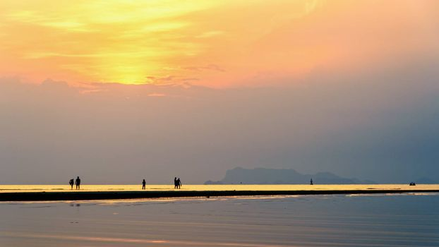 Silhouette of people relaxing on the beach watching the beautiful natural landscape colorful sky and sea during a sunset at Nathon Sunset Viewpoint in Ko Samui, Surat Thani, Thailand, 16:9 widescreen