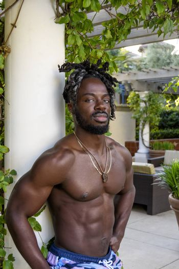 Handsome young muscular African American man posing shirtless outside.
