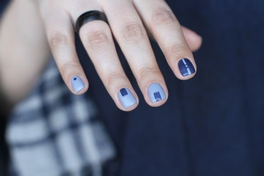 Beautiful female hand with extraordinary manicure. Creative nail design in blue. Ultra stylish colors of nail polish.