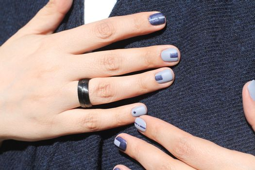 Beautiful female hands with extraordinary manicure. Creative nail design in blue. Ultra stylish colors of nail polish.