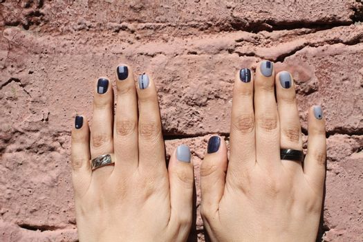 Beautiful female hands with extraordinary manicure on a brick wall. Creative nail design in blue. Ultra stylish colors of nail polish.