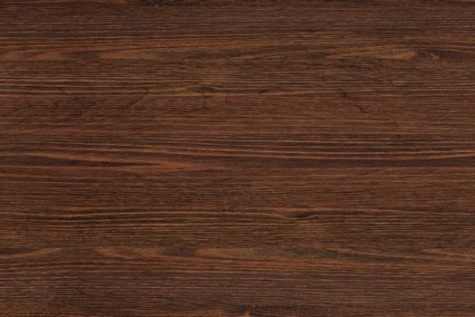 Brown wood texture. Abstract background. Dark brown scratched wooden cutting board.