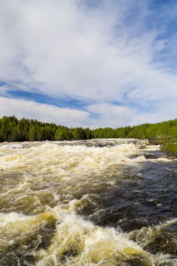 The rapids at Renforsen in Vindeln, Sweden with a partly cloudy sky.