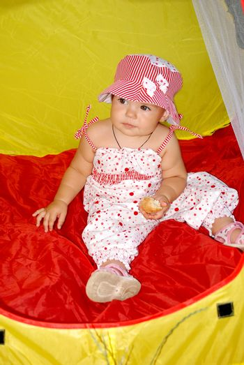 girl in a hat sitting in the red and yellow tent child