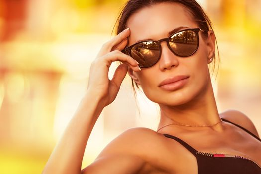 Fashion woman portrait, beautiful girl wearing stylish sunglasses on the beach in bright sunny day, summer vacation look