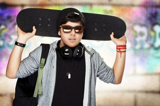 Stylish teen boy with skateboard