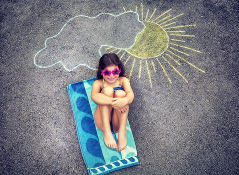 Little girl relaxing on asphalt