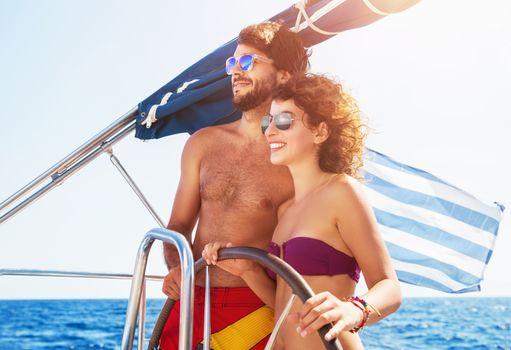 Joyful couple driving sailboat