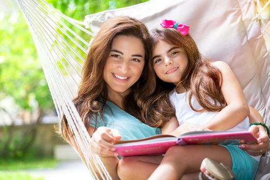Portrait of cheerful mother with baby daughter having fun outdoors, relaxing in hammock and reading funny story, happy family spending time in countryside