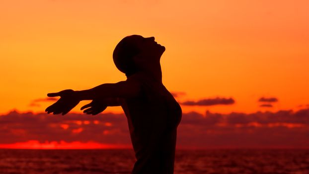 Woman's silhouette on sunset background