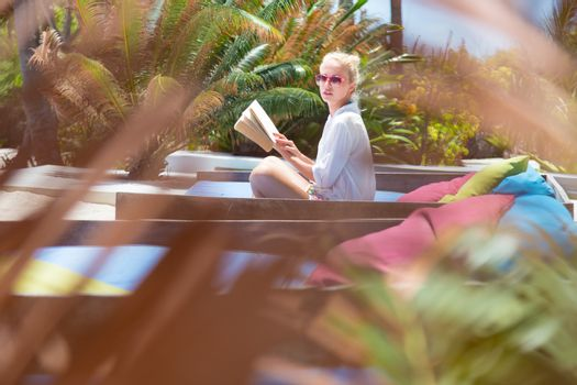Candid shot of lady reading book and relaxing in lush tropical garden.