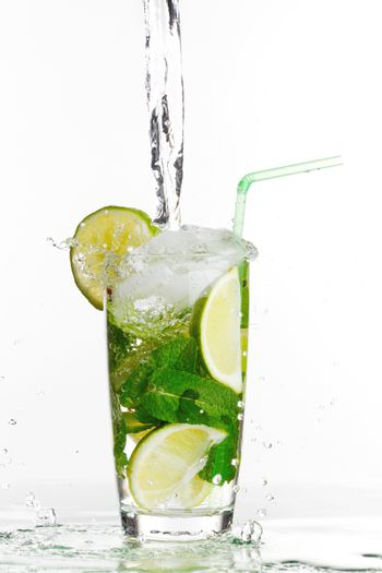 Making mojito cocktail with lime and mint isolated on white background
