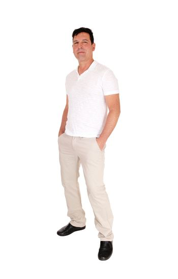A tall handsome middle age man standing in a beige slacks and white t-shirt with his hands in his pocket, isolated for white background