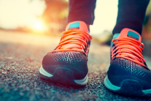 Running in the sunny summer day, closeup photo of a women's sportive shoes, body part, female feet, training outdoors, healthy sportive lifestyle