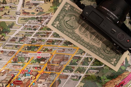 Detail of travel map Flagstaff, Arizona, USA with camera and one Dollar bill, travel planning and preparation concept, Dollar bill just below the couthouse, justice and travel concept