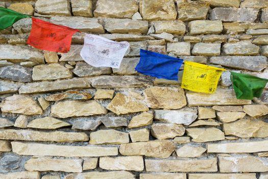 Buddhist prayer flags on stone wall