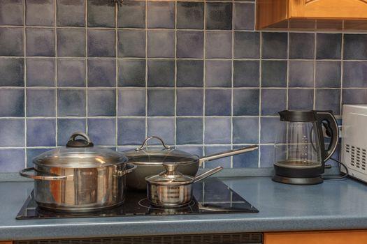 new stainless steel saucepan on modern kitchen range