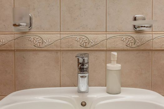Close up of modern faucet and ceramic sink in bathroom