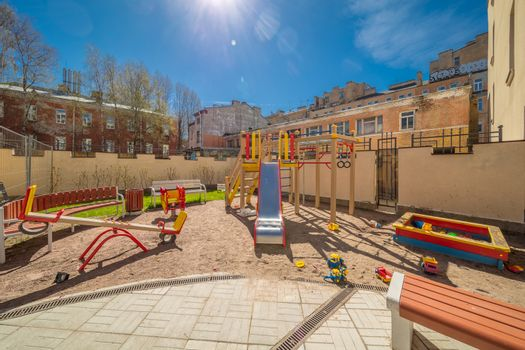 Colorful playground equipment for children in public yard in summer