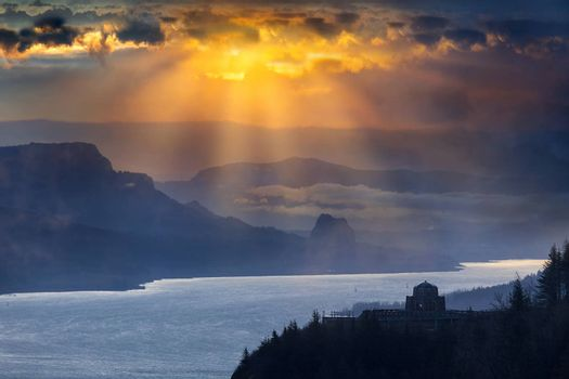 Sun rays over Crown Point and Beacon Rock along Columbia River Gorge during sunrise