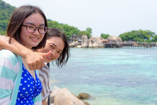 Daughter and mother is lifting thumb admire the beautiful scenery near the sea of the Koh Nang Yuan island is a famous tourist attraction in the Gulf of Thailand, Surat Thani, Thailand