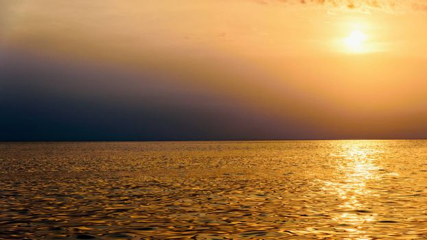 Beautiful nature landscape of colorful sky and warm orange light of the sun at sunset over the sea during summer for background in Thailand, 16:9 widescreen