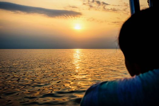Woman watching beautiful nature landscape of colorful sky and warm orange light of the sun at sunset over the sea during summer in Thailand