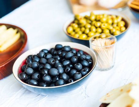 Black and green olives in bowls on white table