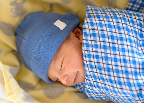 Cute Eurasian newborn baby smiling in his sleep