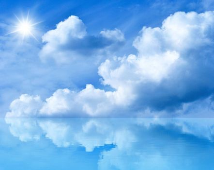 Summer background with blue sky and white clouds. Blue sunny sky above the water. Clouds and the sun are reflected in the water.
