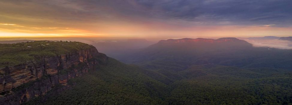 Panorama of the magical sunrise over mist-filled Jamison Valley.  In the distance Mt Solitary cliffs catch the warm light.  Blue Mountains Australia